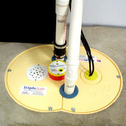 A sump pump system installed in a basement floor.