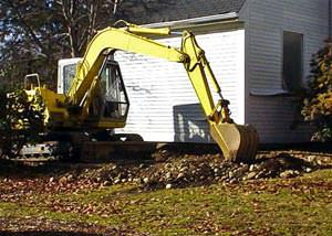 A backhoe excavating a foundation to install weeping tile.