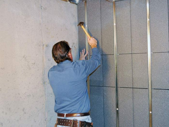 an installer mounting prefinished insulated basement wall panels