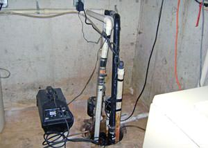 Several sump pumps in a sump pit with too many pipes running at ninety degree angles.