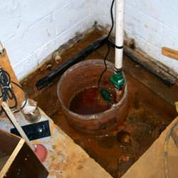 A large sump pit installed in a basement floor.