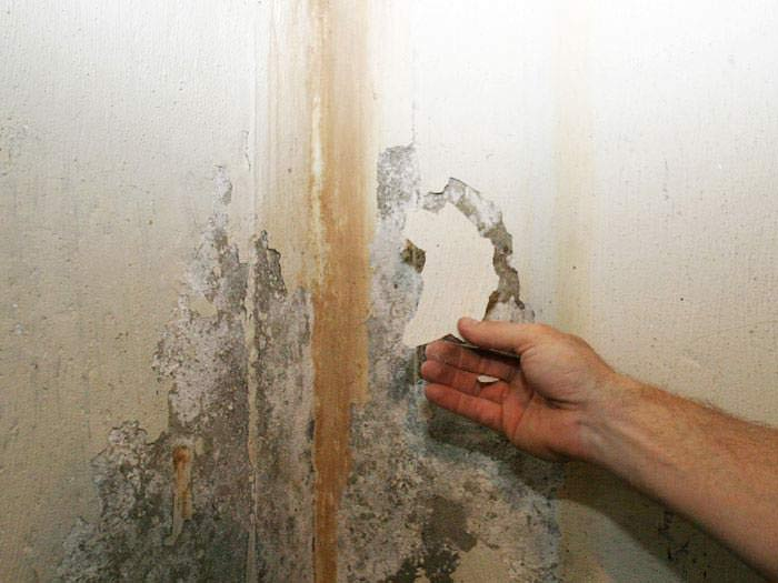 ugly water stained waterproof coatings on a basement wall
